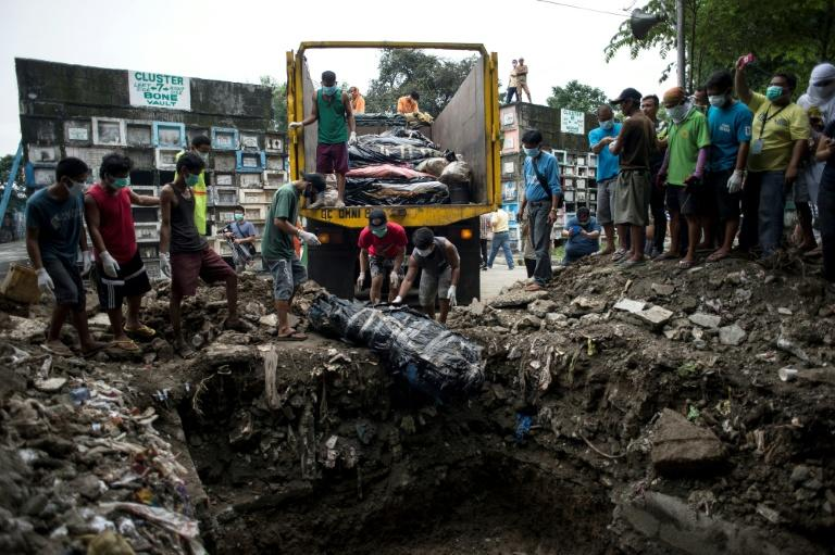 Unclaimed bodies in various stages of decomposition, discovered in a raid by health officials on a funeral home, are buried in a mass grave in Manila