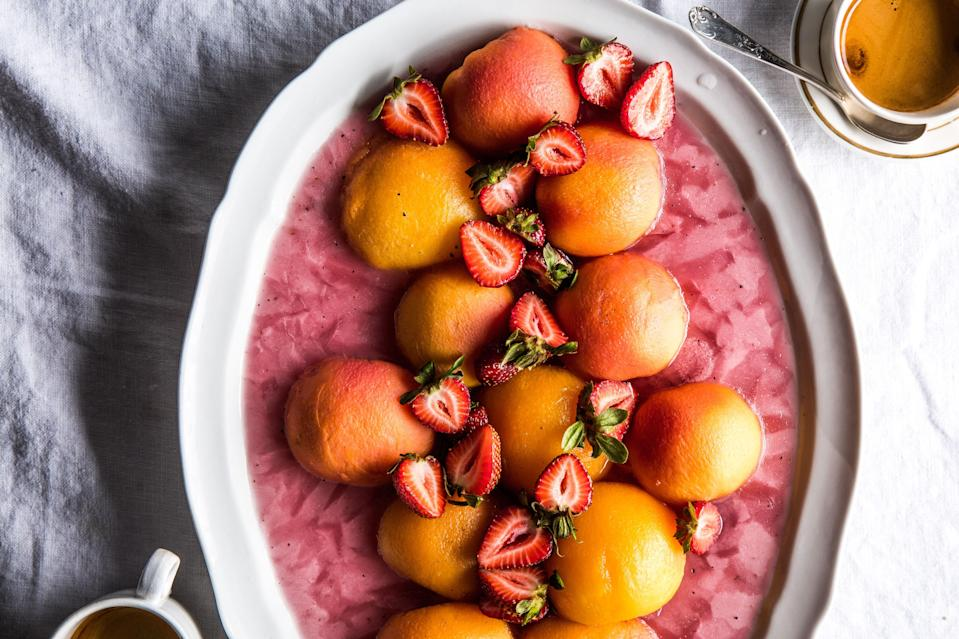 """Poached frozen peaches eat like fruit-shaped sorbet and look like a three-dimensional sunset. <a href=""""https://www.bonappetit.com/recipe/frozen-peaches-with-strawberries-and-mint?mbid=synd_yahoo_rss"""" rel=""""nofollow noopener"""" target=""""_blank"""" data-ylk=""""slk:See recipe."""" class=""""link rapid-noclick-resp"""">See recipe.</a>"""