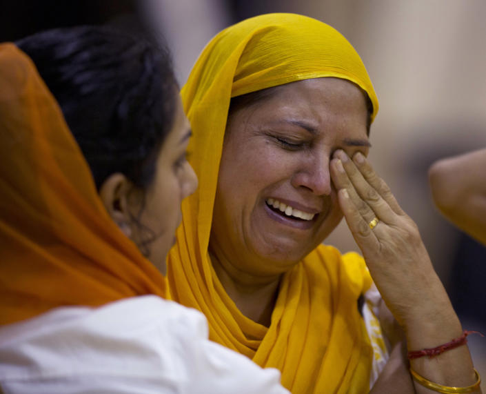 Mourners weep at the funeral and memorial service for the six victims of the Sikh temple of Wisconsin mass shooting in Oak Creek, Wis., Friday, Aug 10, 2012. The public service was held in the Oak Creek High School. Three other people were wounded in the shooting last Sunday at the temple. Wade Michael Page, 40, killed five men and one woman, and injured two other men. Authorities say Page then ambushed the first police officer who responded, shooting him nine times and leaving him in critical condition. A second officer then shot Page in the stomach, and Page took his own life with a shot to the head. (AP Photo/Jeffrey Phelps)