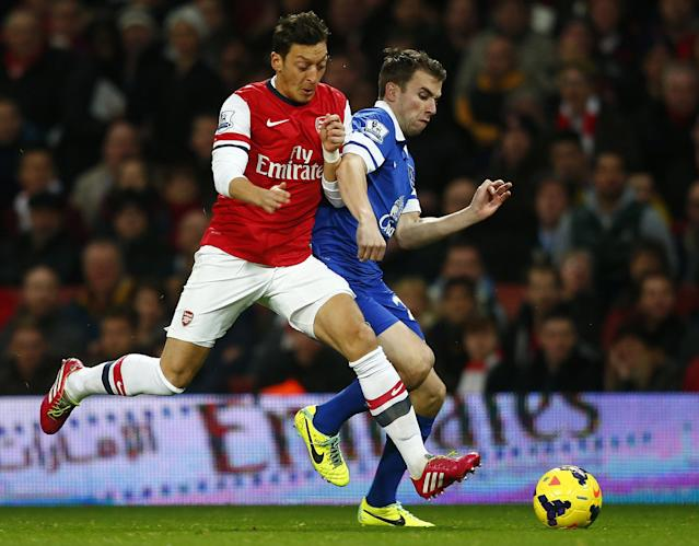"Everton's Seamus Coleman (R) challenges Arsenal's Mesut Ozil during their English Premier League soccer match at The Emirates in London, December 8, 2013. REUTERS/Andrew Winning (BRITAIN - Tags: SPORT SOCCER) FOR EDITORIAL USE ONLY. NOT FOR SALE FOR MARKETING OR ADVERTISING CAMPAIGNS. NO USE WITH UNAUTHORIZED AUDIO, VIDEO, DATA, FIXTURE LISTS, CLUB/LEAGUE LOGOS OR ""LIVE"" SERVICES. ONLINE IN-MATCH USE LIMITED TO 45 IMAGES, NO VIDEO EMULATION. NO USE IN BETTING, GAMES OR SINGLE CLUB/LEAGUE/PLAYER PUBLICATIONS"