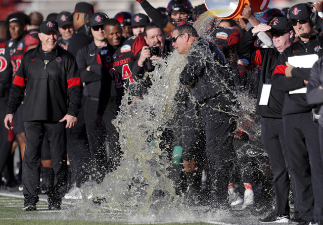 San Diego State assistant coach Brady Hoke is doused as head coach Rocky Long, left, looks on at the end of the New Mexico Bowl NCAA college football game against Central Michigan on Saturday, Dec. 21, 2019 in Albuquerque, N.M. San Diego State won 48-11. (AP Photo/Andres Leighton)