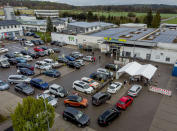 Cars with people waiting for AstraZeneca vaccination queue in front of a tent on the parking lot of a supermarket in Pforzheim, southern Germany, Wednesday, May 5, 2021. A doctor who could not get rid of her AstraZeneca vaccine in her doctor's office decided to offer some 250 doses in drive-in location at the supermarket. (AP Photo/Michael Probst)