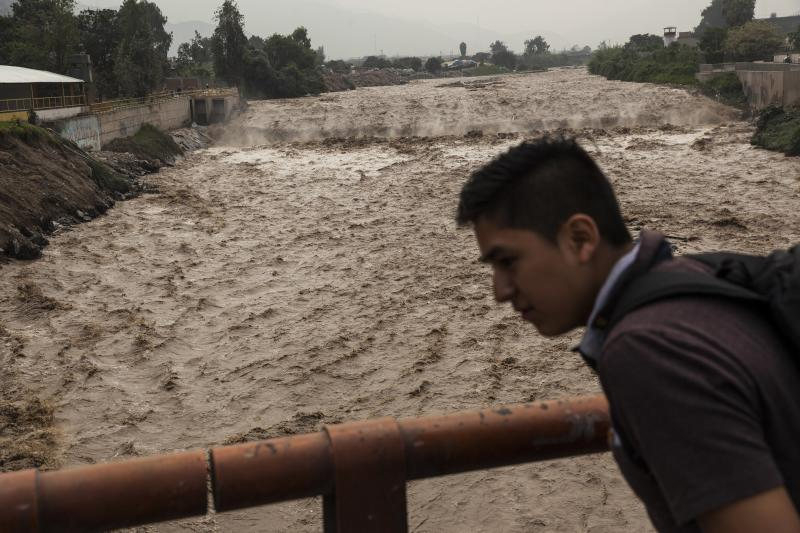 A man looks at the flow of the Huaycoloro river in Lima, Peru, Thursday, March 16, 2017. A new round of unusually heavy rains has killed at least a dozen people in Peru and now threatens flooding in the capital. Authorities said Thursday they expect the intense rains caused by the warming of surface waters in the eastern Pacific Ocean to continue another two weeks. (AP Photo/Rodrigo Abd)