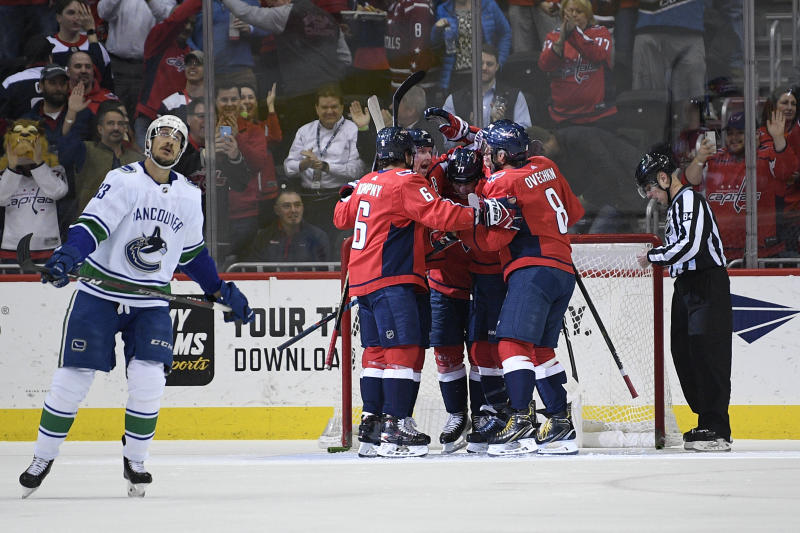 Washington Capitals left wing Alex Ovechkin (8), of Russia, defenseman Michal Kempny (6) and other celebrate a goal by right wing T.J. Oshie (77) during the first period of an NHL hockey game against the Vancouver Canucks, Tuesday, Feb. 5, 2019, in Washington. (AP Photo/Nick Wass)
