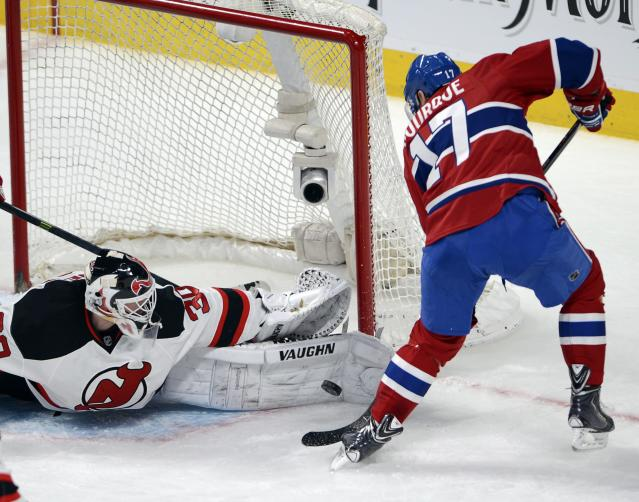 New Jersey Devils goalie Martin Brodeur (30) stops Montreal Canadiens left wing Rene Bourque (17) during second period National Hockey League action, Tuesday, Jan. 14, 2014, in Montreal. (AP Photo/The Canadian Press, Ryan Remiorz)
