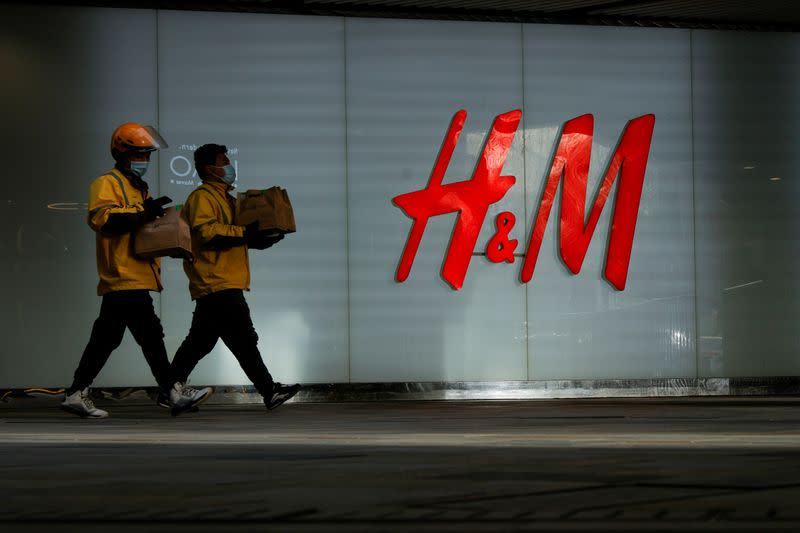 FILE PHOTO: People walk past an H&M store in a shopping area in Beijing