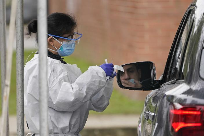 Medical personnel prepare to administer a COVID-19 swab at a drive-through testing site in Lawrence, N.Y., Wednesday, Oct. 21, 2020. The rate of COVID-19 infections has risen enough in New Jersey, Pennsylvania and Connecticut to require those states' residents to quarantine if they travel to New York, but Gov. Andrew Cuomo says New York won't enforce the rules against those residents. (AP Photo/Seth Wenig)