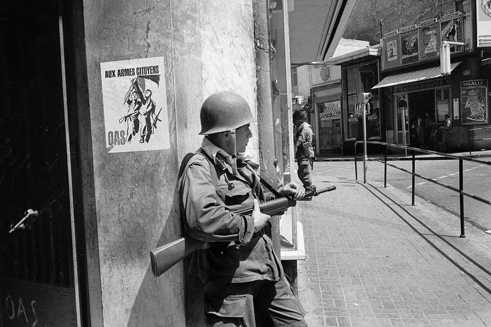 FILE - In this May 15, 1962 file photo, a French soldier guards a street corner in Oran, Algeria. French President Emmanuel Macron announced a decision to speed up the declassification of secret documents related to Algeria's seven-year war of independence from 1954 to 1962. On the wall is a poster of the nationalist Secret Armed Organization, calling for citizens to take up arms against Algerian independence. (AP Photo/Horst Faas, File)