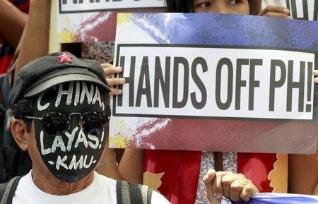 """An activist wears a black mask with a message reading """"China Get Out!"""" as they protest against Beijing's activities in the South China Sea outside the Chinese consulate in Makati city"""