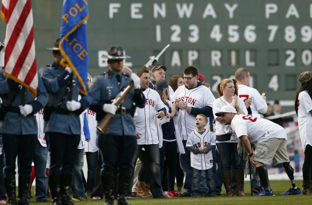 Boston Marathon bombing survivors including Marc Fucarile, lower right, gather on the field at Fenway Park during ceremonies marking the one-year anniversary of the bombing before a baseball game between the Boston Red Sox and the Baltimore Orioles in Boston, Sunday, April 20, 2014. (AP Photo/Michael Dwyer)