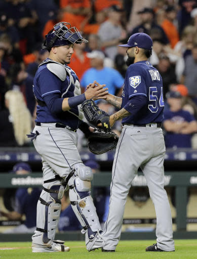 Tampa Bay Rays' Sergio Romo (54) and Jesus Sucre celebrate after a baseball game against the Houston Astros Tuesday, June 19, 2018, in Houston. The Rays won 2-1. (AP Photo/David J. Phillip)