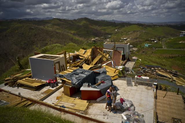 <p>Rafael Reyes embraces his wife Xarelis Negron and his son Xariel as they stand next to thier belongings, in front of the remains of their home destroyed by Hurricane Maria, in the San Lorenzo neighborhood of Morovis, Puerto Rico, Saturday, Oct. 7, 2017. The Reyes family lost all their belongings and their house, and are looking forward to being able to rebuild and continue their life. (Photo: Ramon Espinosa/AP) </p>