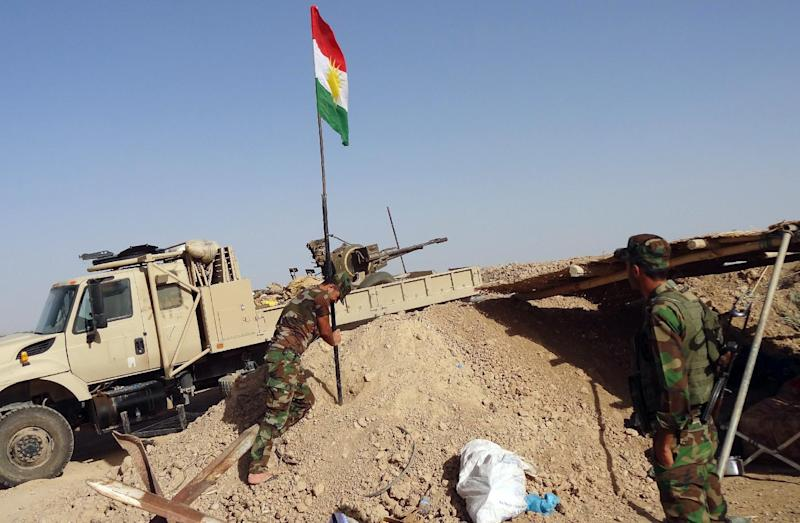 Kurdish Peshmerga forces raise the Kurdish flag at a checkpoint on the road leading from Kirkuk to northern Iraqi city of Tikrit on June 30, 2014 (AFP Photo/Marwan Ibrahim )