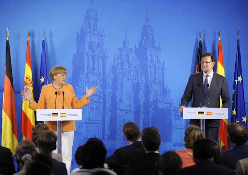German Chancellor Angela Merkel (L) and Spanish Prime Minister Mariano Rajoy give a joint press conference after their meeting in Santiago de Compostela, on August 25, 2014