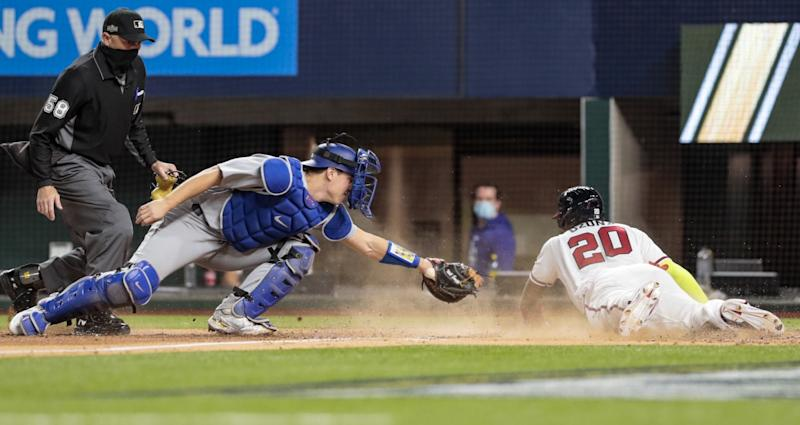 Atlanta Braves designated hitter Marcell Ozuna slides into home past Dodgers catcher Will Smith.