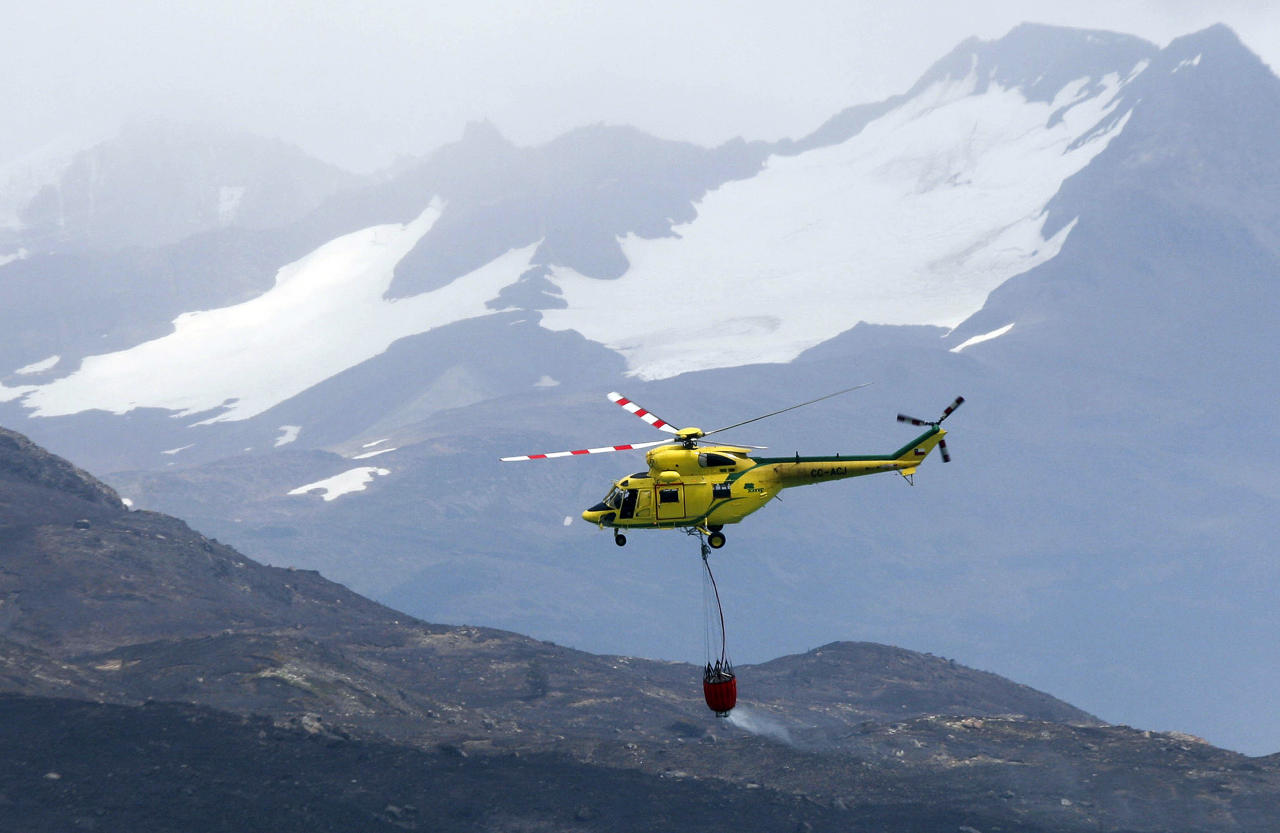 A helicopter works to dampen an area of the Torres del Paine national park in Torres del Paine, Chile, Sunday Jan. 1, 2012. Firefighters are making progress against a major blaze that has burned at least 48 square miles (12,500 hectares) in one of Chile's most spectacular national parks. The Israeli tourist accused of setting the fire denied guilt. (AP Photo)