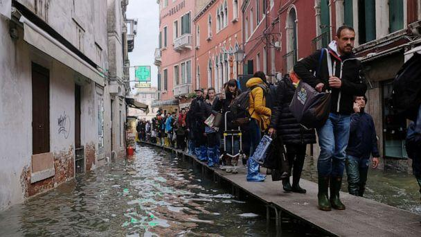 PHOTO: People walk on a catwalk in the flooded street during a period of seasonal high water in Venice, Italy, Nov. 15, 2019. (Manuel Silvestri/Reuters)