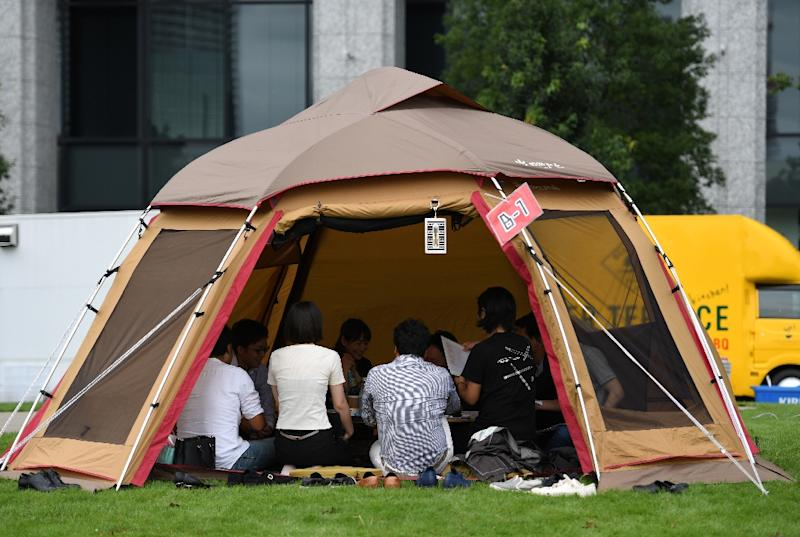 Tiny one-person cubicles in underground stations, camping tents under towering skyscrapers and even karaoke clubs are popping up as alternative workspaces all over Japan (AFP Photo/Toshifumi KITAMURA)
