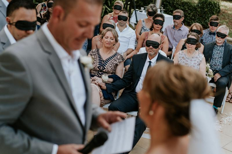Wedding guests wear black blindfolds during the ceremony. One woman in the center of the shot is not wearing a blindfold: Agnew's mom, who also has cone-rod dystrophy. In the foreground and out of focus, you can see the groom in a gray suit and the bride in a veil with her hair pulled back in a chignon. (James Day Photography)