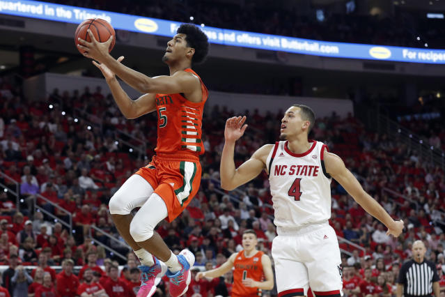 Miami guard Harlond Beverly (5) drives for a basket while North Carolina State forward Jericole Hellems (4) defends during the second half of an NCAA college basketball game in Raleigh, N.C., Wednesday, Jan. 15, 2020. (AP Photo/Gerry Broome)