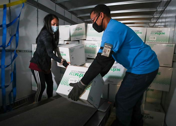 UPS package handlers Jesirae Elzey and Demeatres Ralston unload boxes of the Moderna COVID-19 vaccine at UPS Worldport in Louisville, Ky.
