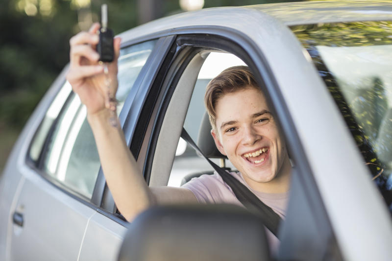 Happy learner driver cheering and holding car key