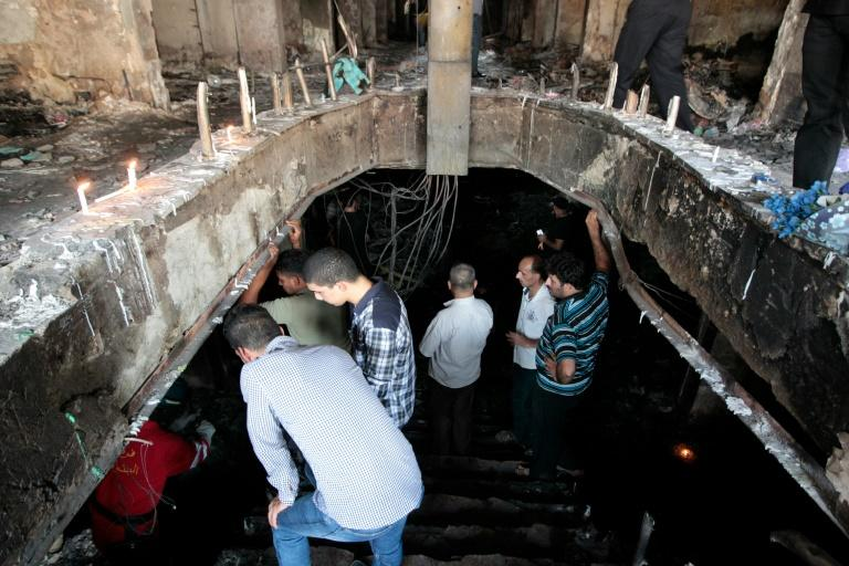 Iraqis look at members of the civil defence searching for bodies on July 5, 2016, at the site of the suicide-bombing attack which took place two days earlier in Baghdad's Karrada neighbourhood