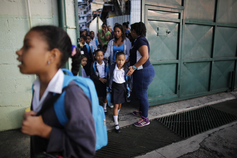 In this Oct. 2, 2019 photo, children enter school on their first day of class at the Jerman Ubaldo Lira public school in Caracas, Venezuela. Principal Erika Tortosa said that she has trouble finding enough teachers, who endure the same hardships that drive away the students' families. (AP Photo/Ariana Cubillos)