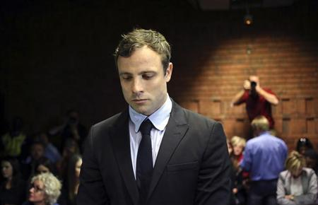 Olympic and Paralympic running star Oscar Pistorius stands during court proceedings at the Pretoria Magistrates cour