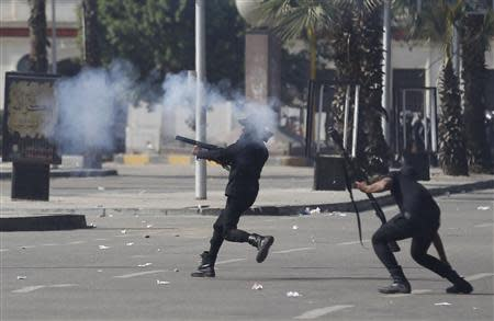 Riot police fire rubber bullets and tear gas during a demonstration at the front of Cairo University