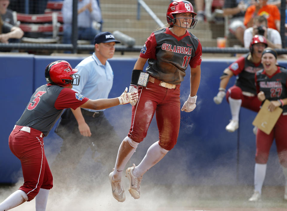 FILE - Oklahoma's Nicole Mendes (11) and Kelsey Arnold (3) celebrate scoring in the fifth inning during the Women's College World Series softball game between the against Oregon at ASA Hall of Fame Stadium in Oklahoma City, in this Sunday, June 4, 2017. Division I softball is providing a training ground this season for players preparing for the 2021 Olympics. Oklahoma's Nicole Mendes and North Carolina State's Tatyana Forbes will play for Mexico, their schools said. (Sarah Phipps/The Oklahoman via AP, File)