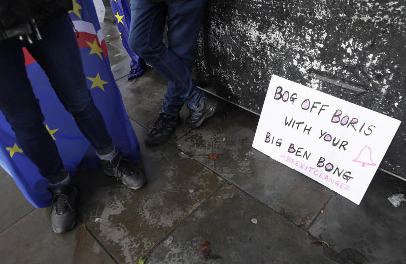 A banner alongside anti Brexit campaigners outside Parliament in London, Wednesday, Jan. 15, 2020.  The Big Ben bell of Britain's Parliament has been largely silent since 2017 while its iconic clock tower undergoes four-years of renovation. Brexit-backing lawmakers are campaigning for it to strike at the moment Britain leaves the European Union at 11 p.m. (2300GMT) on Jan. 31,  but some campaigners and officials say it is not worth the cost, which has been estimated at around 500,000 pounds (dollars 650,000 US). (AP Photo/Kirsty Wigglesworth)