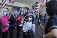 FILE - In this July 14, 2021 file photo, Simone Biles walks to her gate for her flight to the Summer Olympic Games in Tokyo as United Airlines employees wave flags during a send-off event for the U.S. Women's Gymnastics team at the San Francisco International Airport. Biles and Naomi Osaka are prominent young Black women under the pressure of a global Olympic spotlight that few human beings ever face. But being a young Black woman -- which, in American life, comes with its own built-in pressure to perform -- entails much more than meets the eye. (AP Photo/Eric Risberg, File)