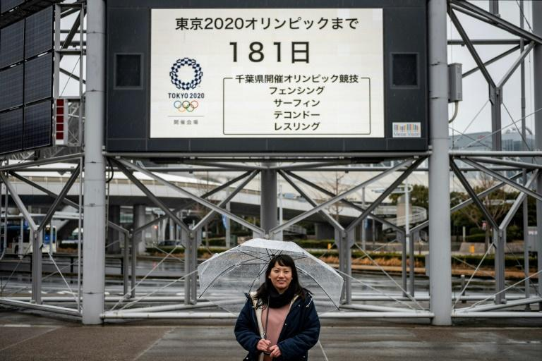 Tarumi posing in front of an Olympic countdown clock, fears the Games' message of hope and equality could be lost