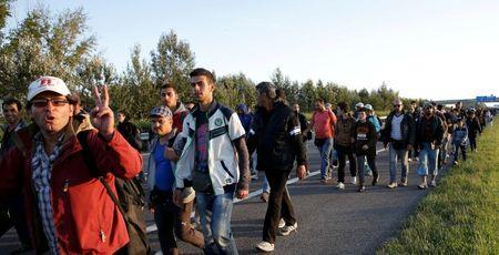 A group of migrants walks against the traffic on a motorway leading to Budapest as they left a transit camp in the village of Roszke, Hungary, September 7, 2015. REUTERS/Marko Djurica
