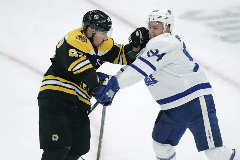 Boston Bruins center Brad Marchand, left, and Toronto Maple Leafs defenseman Tyson Barrie (94) tangle during the first period of an NHL hockey game in Boston, Tuesday, Oct. 22, 2019. (AP Photo/Charles Krupa)