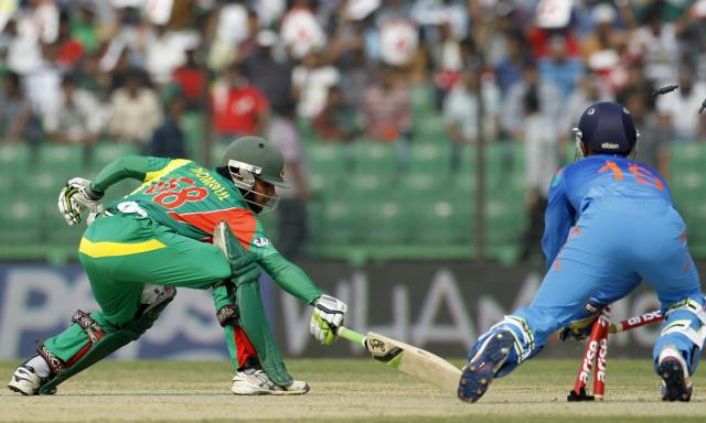 Bangladesh's Mominul Haque (L) tries to make his ground as India's wicketkeeper Dinesh Karthik breaks the wickets to dismiss him successfully during their Asia Cup 2014 one-day international (ODI) cricket match in Fatullah February 26, 2014. REUTERS/Andrew Biraj (BANGLADESH - Tags: SPORT CRICKET)