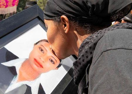 A woman kisses a portrait photo as she mourns during the burial ceremony of the Ethiopian Airline Flight ET 302 crash victims at the Holy Trinity Cathedral Orthodox church in Addis Ababa, Ethiopia, March 17, 2019. REUTERS/Maheder Haileselassie