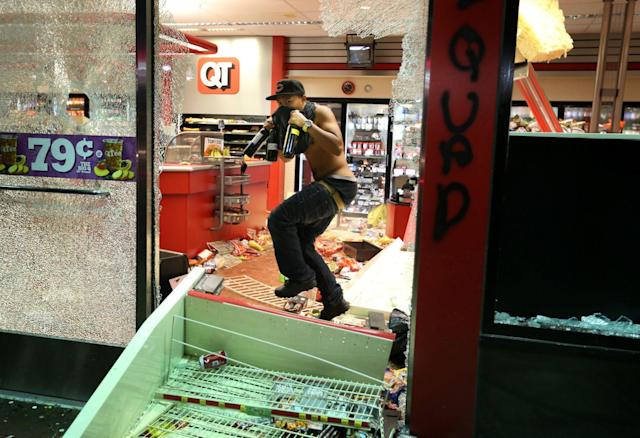 <p>A looter takes items from inside the QuikTrip in 9400 block of W. Florissant Avenue in Ferguson, Missouri on August 10, 2014. The looters later burned the store. (David Carson/St. Louis Post-Dispatch/TNS/ZUMA Wire) </p>