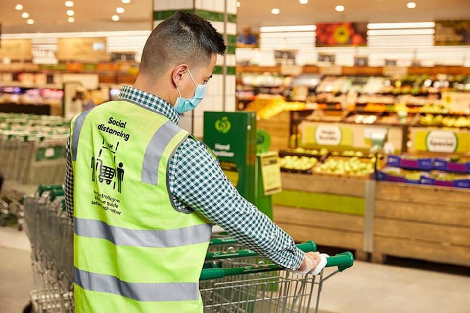 Woolworths worker disinfects a shopping trolley. Source: Woolworths Group