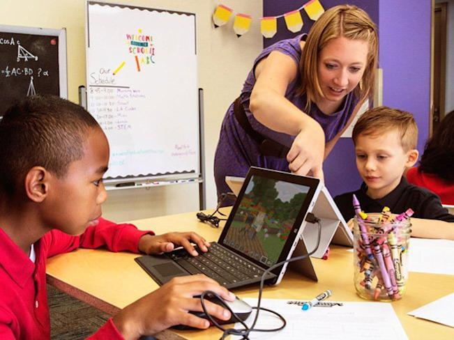 Kids enjoy learning via Minecraft, while a parent stands nearby willing to help them along.