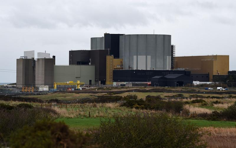 The Wylfa Newydd nuclear power station is pictured beyond farmer's fields on Anglesey, north-west Wales - AFP