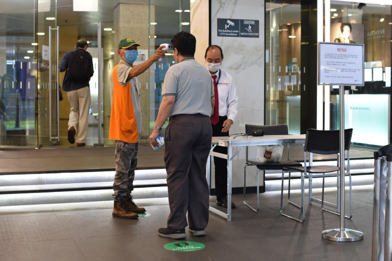 A man wearing a face mask uses a thermal scanner to check on the temperature of an individual before he can enter a building in Singapore Tuesday, June 2, 2020. Singapore reopened 75 percent of its economy Tuesday, as part of a three-phase controlled approach to end a virus lockdown since early April. (AP Photo/YK Chan)
