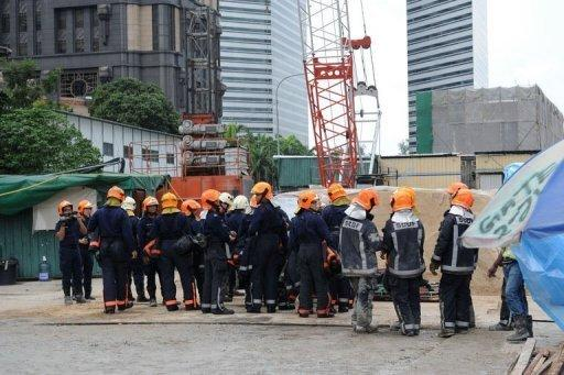 Singaporean rescuers gather outside the Downtown Line (DTL) Bugis Station subway construction site in Singapore on July 18, 2012. Two workers were killed and eight others injured in Singapore when the scaffolding at a subway construction site collapsed on Wednesday, civil defence officials said