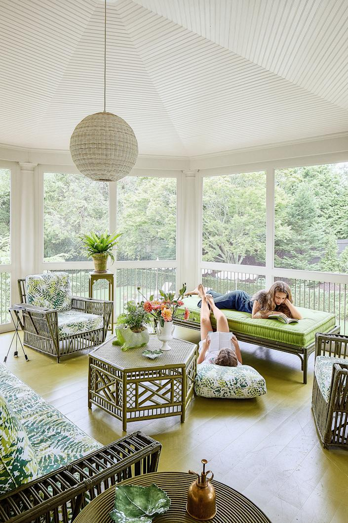 """<div class=""""caption""""> Beatriz (right) and Frederica lounge on the screened porch, decorated with a vintage rattan cocktail table and seating. <a href=""""https://www.anthropologie.com/"""" rel=""""nofollow noopener"""" target=""""_blank"""" data-ylk=""""slk:Anthropologie"""" class=""""link rapid-noclick-resp"""">Anthropologie</a> bench; <a href=""""https://www.serenaandlily.com/"""" rel=""""nofollow noopener"""" target=""""_blank"""" data-ylk=""""slk:Serena & Lily"""" class=""""link rapid-noclick-resp"""">Serena & Lily</a> pendant. </div>"""