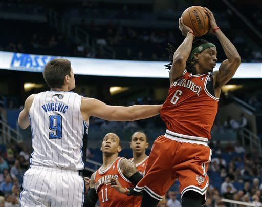 Milwaukee Bucks' Marquis Daniels (6) looks to pass the ball as he is guarded by Orlando Magic's Nikola Vucevic (9), of Montenegro, during the first half of an NBA basketball game, Wednesday, April 10, 2013, in Orlando, Fla. (AP Photo/John Raoux)