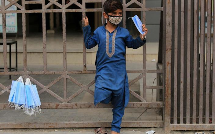 A boy sells protective masks on a road as Pakistan government makes face masks mandatory in public place amid third wave of coronavirus, in Peshawar - ARSHAD ARBAB/EPA-EFE/Shutterstock