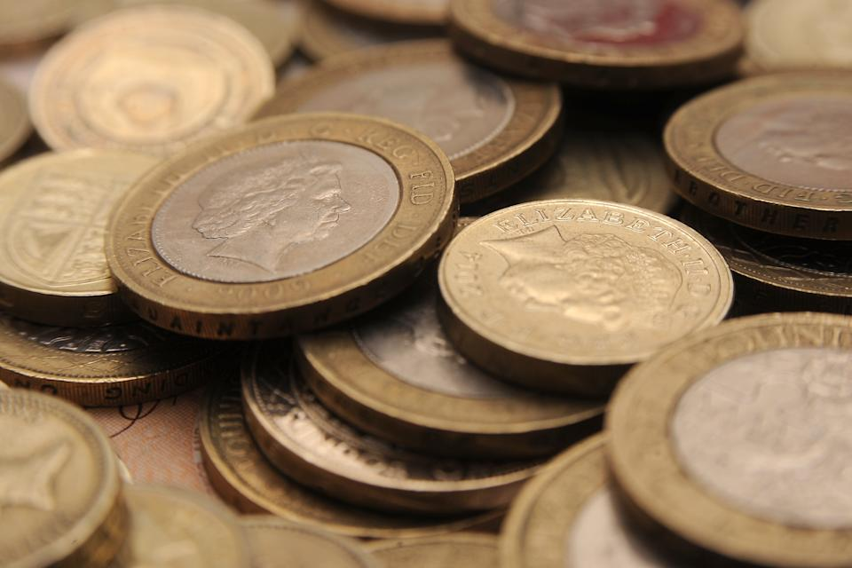 A selection of one pound coins, two pound coins and bank notes