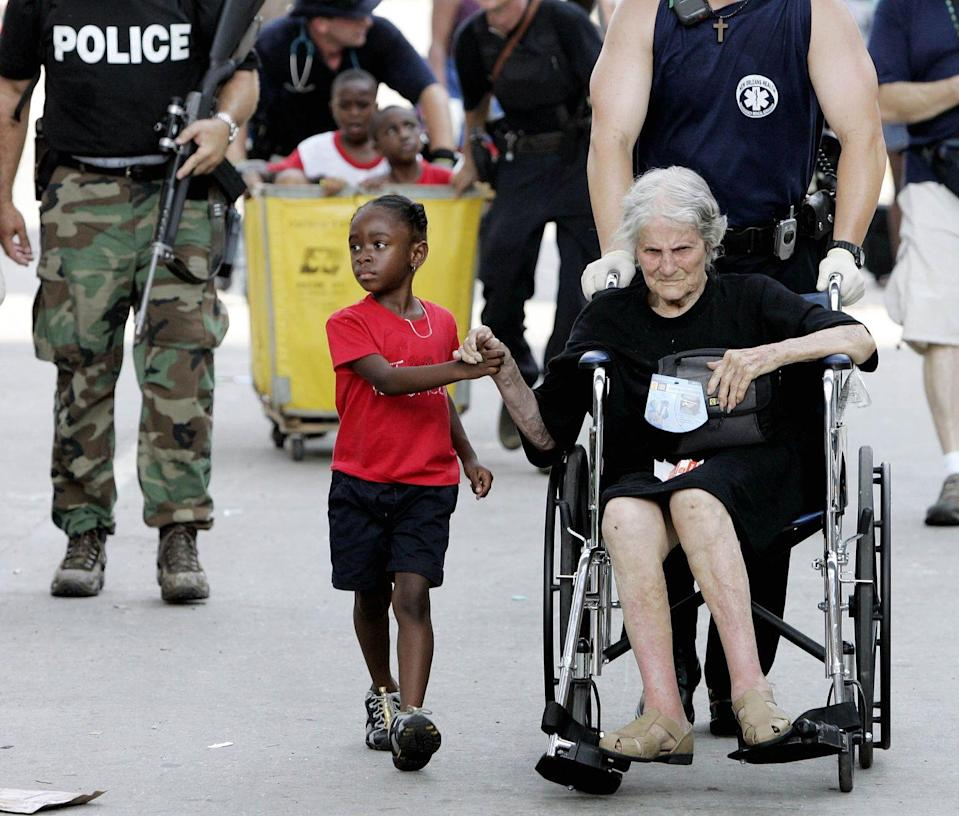 <p>2005. AP Caption: Tanisha Belvin, 5, holds the hand of fellow Hurricane Katrina victim Nita LaGarde, 89, as they are evacuated from the Convention Center in New Orleans. Hundreds of people waited several days to be evacuated. </p>