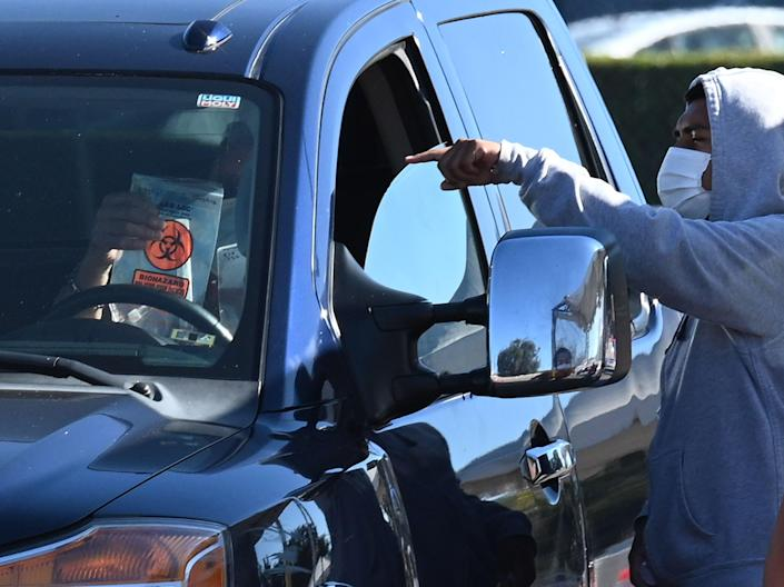 In this file photo taken on 17 November 2020 a Covid-19 testing site staff member explains how to take a self-administered coronavirus test to a person in their car at a drive-up testing site in Los Angeles, California ((AFP via Getty Images))